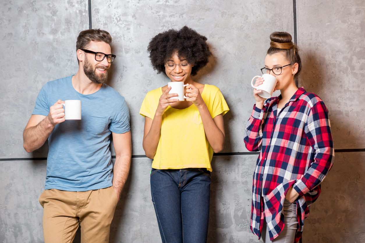 Three young workers talking over coffee